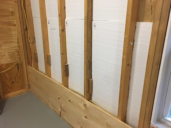 The studs behind a wall with a Styrofoam panels inbetween them with the first two wood boards from the wall across the bottom nailed in. The floor is painted gray.