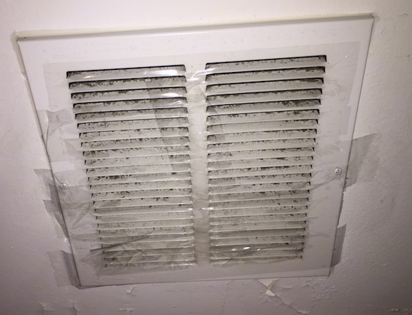 A white ceiling vent taped over with clear packing tape with gray fiberglass dust sticking to the sticky side.