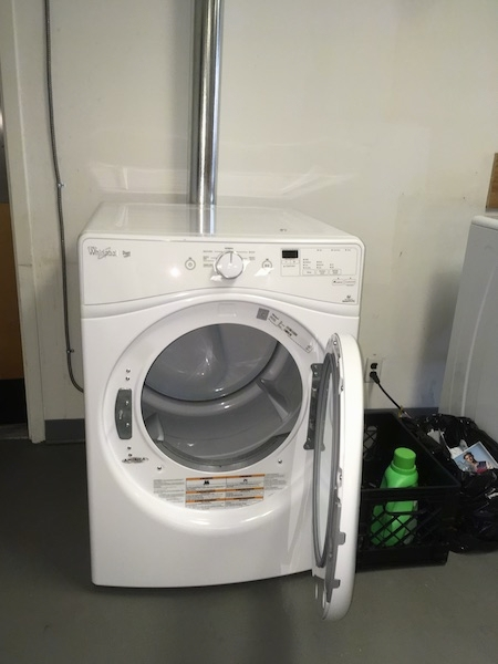 A white dryer sitting on a gray floor with a silver dryer tube running up the wall to the outside of the room. The dryer door is open. There is a black milk crate with a green bottle of Gain laundry soap in it on the floor next to the dryer.