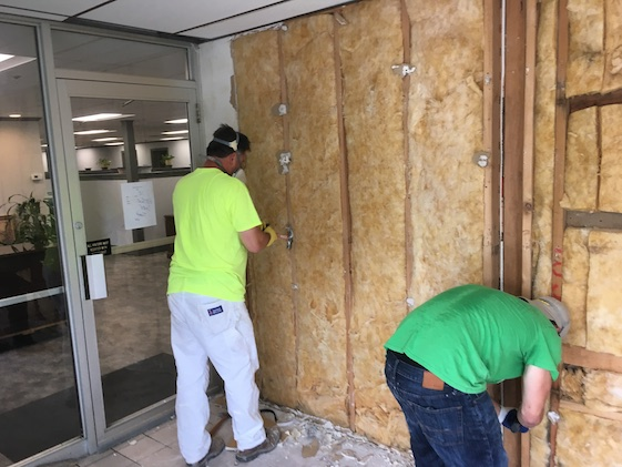 Two men standing in a vestibule with masks on as they remove the drywall showing the yellow fiberglass.