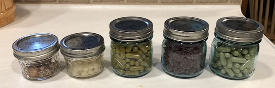 Five little mason jars sitting on white counter with vitamins in them