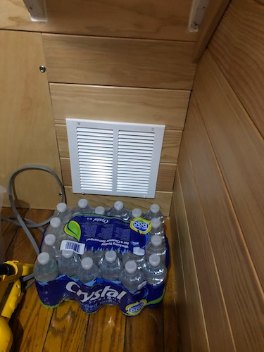 A case of water bottles in a closet next to a white vent