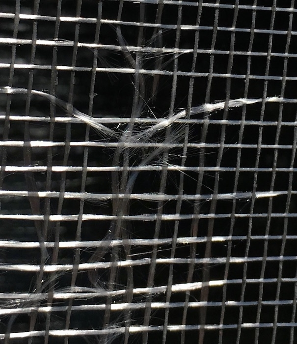 Close up of a window screen with glass fiber strands fraying.