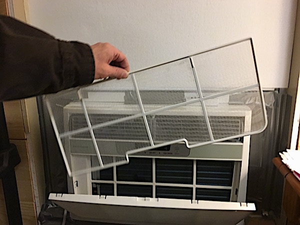 A white Frigidaire window heat pump unit inside of a window with the front panel open and a person pulling out a screen-like filter.