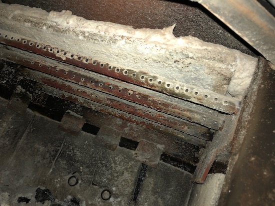A view of the catalytic converter inside of the wood burning stove with a bat of ceramic insulation laying on top of it.
